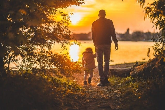A father walking holding the hand of his son, sunset in the background